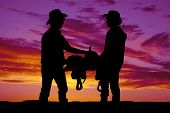 Постер, плакат: Silhouette Of Two Cowboys Holding A Saddle In The Sunset