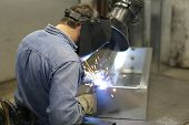 image of people welding  - worker is welding box with gloved hands - JPG