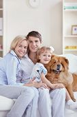 pic of family fun  - Happy young family with dog at home - JPG