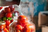 Tomatoes being swamped boiled water in process of canning. Canned tomato - good winter vegeterian fo