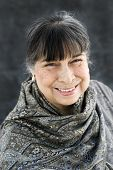 stock photo of senora  - portrait of a hispanic grandmother in a grey scarf smiling - JPG