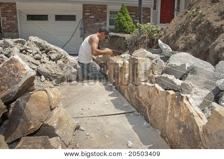 Mason building a rock wall