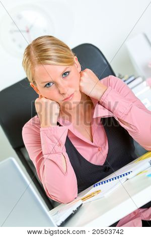 Bored modern business woman sitting at office desk and keep head on hands