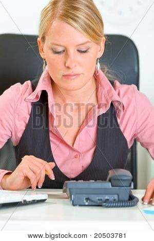 Concentrated modern business woman sitting at office desk and expecting phone call