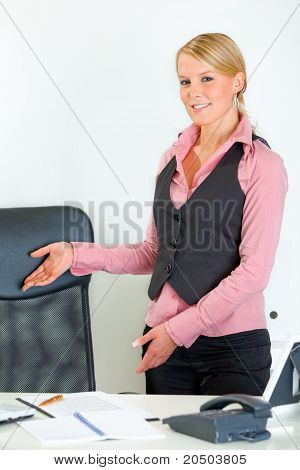 Smiling modern business woman standing near office desk and inviting to sit on chair