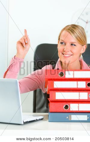 Sitting at office desk with pile of folders smiling modern business woman showing idea gesture
