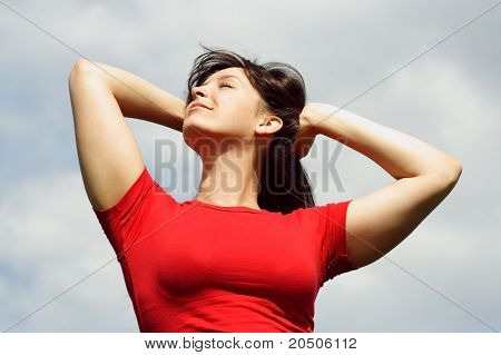 Young Girl In Red Shirt Smiling, Hands Beyond Head, Eyes Closed, Cloudy Sky