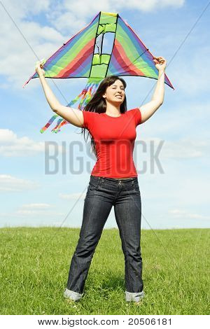 Young Girl In Red Shirt Standing On Summer Meadow And Holding Kite Above Head