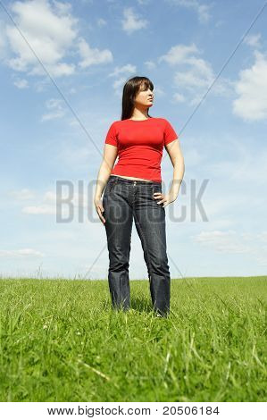 Young Girl In Red Shirt Standing On Summer Meadow, Blue Sky