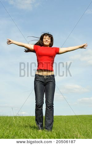 Young Girl In Red Shirt Standing On Summer Meadow, Hands Apart, Blue Sky