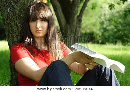 Young Brunette Girl In Red Shirt Siting Near Tree And Reading Book, Outdoor