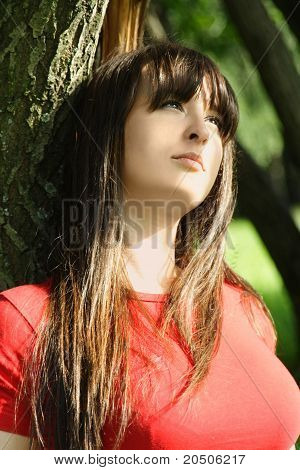 Young Brunette Girl In Red Shirt Siting Near Tree And Looking At Side