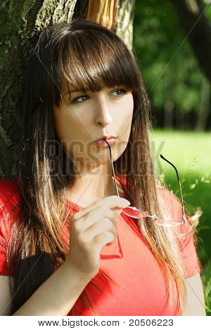 Young Brunette Girl In Red Shirt Siting Near Tree And Looking At Side, Holding Glasses