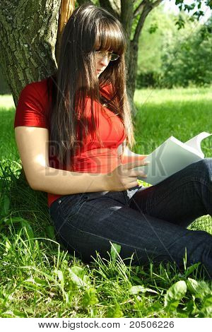 Young Brunette Girl In Glasses And Red Shirt Sitting Near Tree And Reading A Book