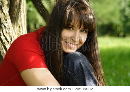Young Brunette Girl In Red Shirt Smiling And Siting Near Tree, Head On Knee