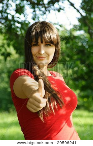 Young Brunette Girl In Red Shirt Making Thumbs Up Gesture, Summer Park