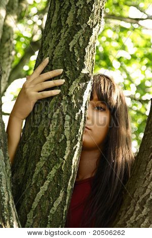 Young Brunette Girl With Long Hair Looking Out Behind Summer Tree