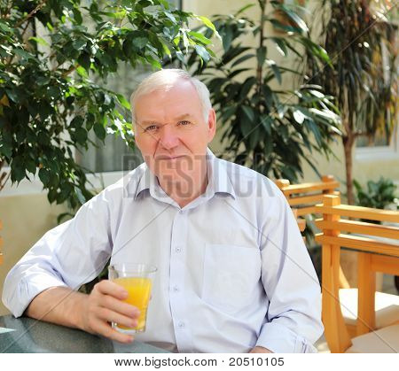 portrait of old man with orange juice outdoors