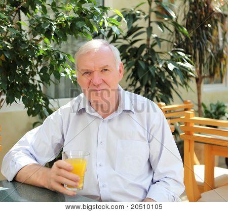 Porträt des alten Mannes mit Orangensaft im freien