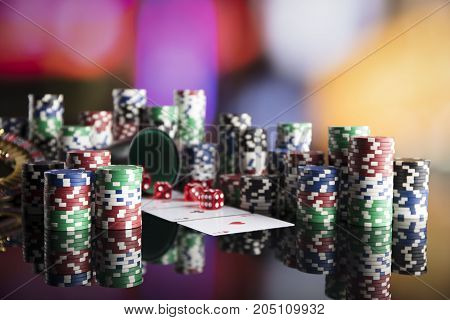 Casino theme. High contrast image of  poker game, dice game, poker chips on a gaming table, all on colorful bokeh background.