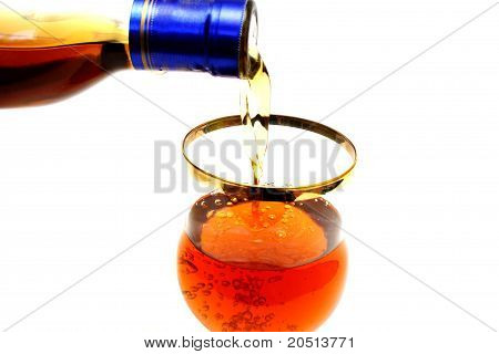 Bottleneck Filling A Glass With Brown Liquid