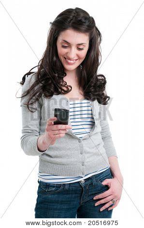 Bella joven sonriente sosteniendo un teléfono inteligente, mientras que la mensajería de texto aislado sobre fondo blanco