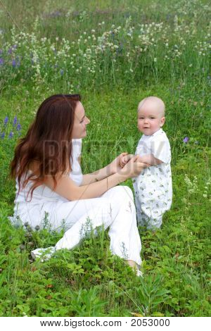Beautiful Woman With Small Kid At Meadow
