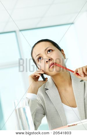Photo of smart businesswoman with pensive expression calling by mobile phone