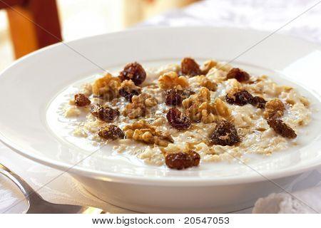 Plato de avena con pasas, nueces y azúcar morena.  Una alimentación saludable.