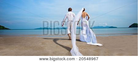 beautiful couple on the beach in wedding dress