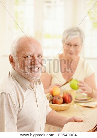 Portrait of smiling older man at kitchen table having breakfast, holding newspaper, with wife in background.?