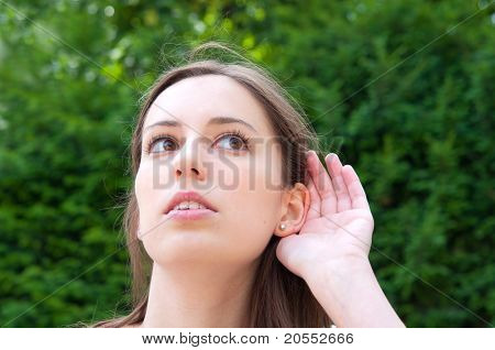Relying on hand-ear listening young woman in the streets of Paris