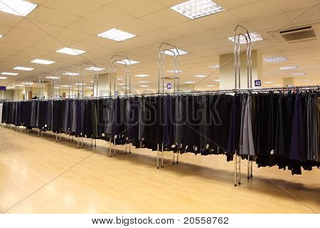 row men trousers on hangers in big light shop; different sizes; School Clothing
