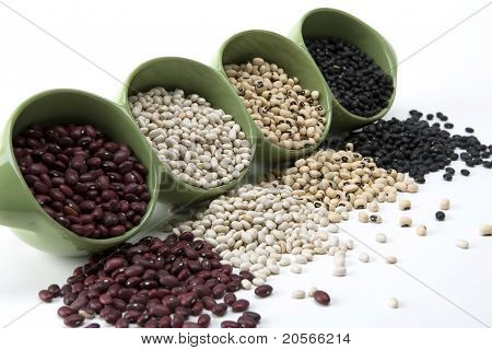 Assorted mixed dried beans spilling from a green ceramic dish