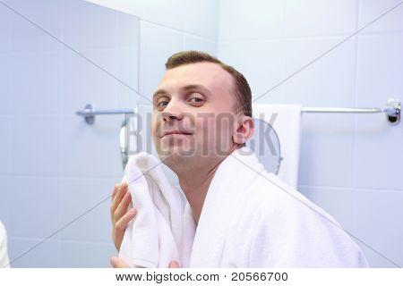 young man in bathroom wearing white bathrobe