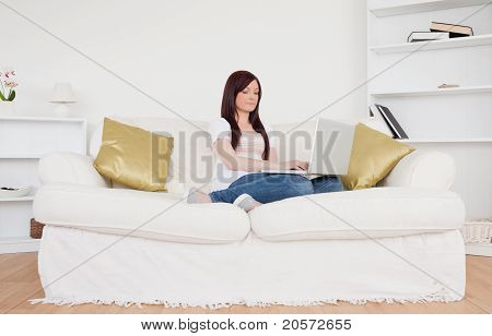 Pretty Red-haired Woman Relaxing With Her Laptop While Sitting On A Sofa