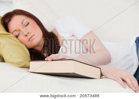 Good Looking Red-haired Girl Having A Rest While Studying On A Sofa