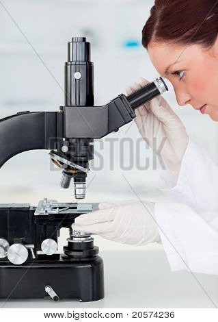 Beautiful Red-haired Scientist Looking Through A Microscope