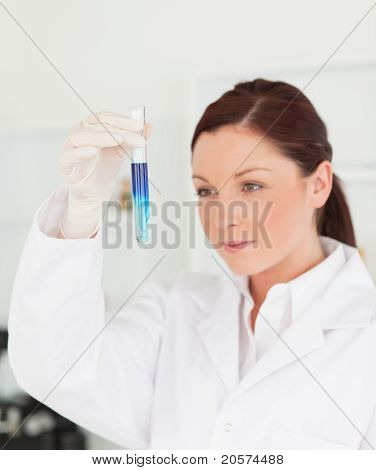 Beautiful Red-haired Scientist Looking At The Camera While Holding A Test Tube