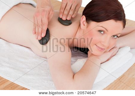 Portrait Of A Good Looking Red-haired Female Posing While Receiving A Massage