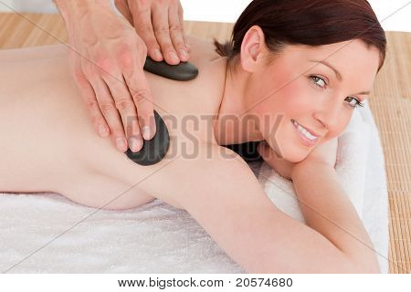 Portrait Of A Charming Red-haired Female Posing While Receiving A Massage