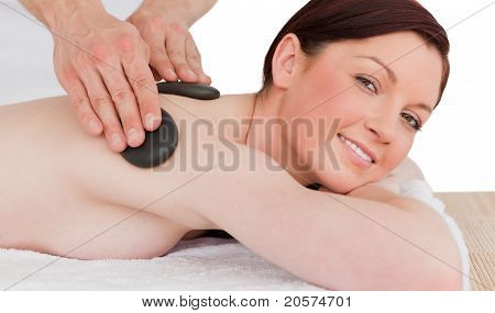 Portrait Of A Gorgeous Red-haired Female Posing While Receiving A Massage