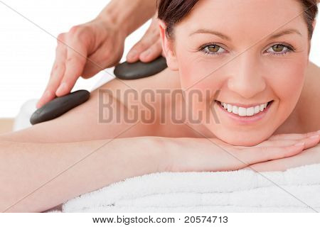 Portrait Of A Smiling Red-haired Female Posing While Receiving A Massage