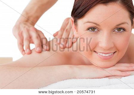 Portrait Of A Happy Red-haired Female Posing While Receiving A Massage
