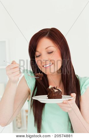 Joyful Red-haired Woman Eating Some Cake In The Kitchen