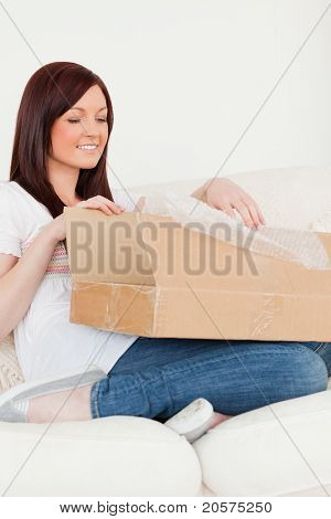 Good Looking Red-haired Woman Opening A Carboard Box While Sitting On A Sofa