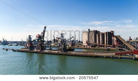 Grain Elevator In Harbour With Terminal And Cranes