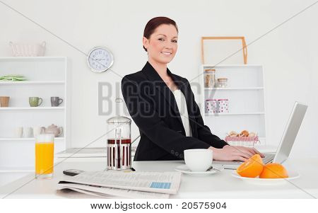 Good Looking Red-haired Female In Suit Relaxing With Her Laptop In The Kitchen