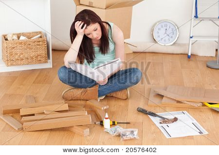 Good Looking Red-haired Girl Being Depressed While Reading A Manual Before Do-it-yourself
