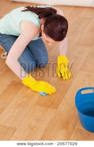 Good Looking Red-haired Woman Cleaning The Floor While Kneeling